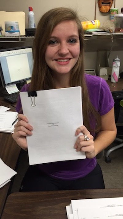 "Baumberger poses with her finished manuscript of what became ""Breaking the Pocket"" on Nov. 30, 2015. (Courtesy of Casey Baumberger)"